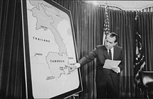 A room with a curtain and an American flag in the background. A man in a suit points to Cambodia on a large standing map of Southeast Asia.