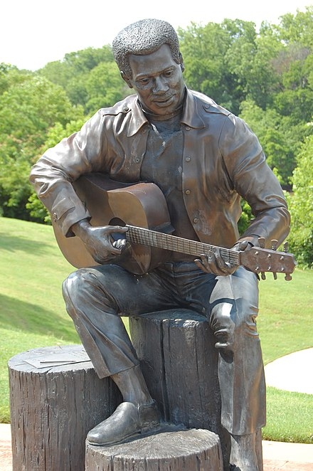 """Otis Redding Sittin' on the Dock of the Bay"", statue in Gateway Park by Bradley Cooley and Bradley Cooley, Jr of Bronze By Cooley, 2003 OtisReddingStatue.jpg"