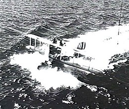 Single-engined military biplane on floats landing in ocean and trailing heavy wake, three-quarters overhead