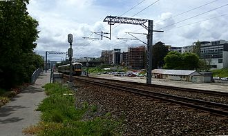 Parnell railway station - The Parnell railway station under construction. View from the Auckland Domain entrance to the station (looking north towards the platforms). An AM class train is passing through the station and one building from the former Mainline Steam depot is visible in the background.