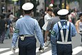 Police officers enforcing rules that maids advertise from the sidewalks and not from the middle of the street, in Akihabara pedestrian zone (2006-07-09 01.22.19 by interiot).jpg