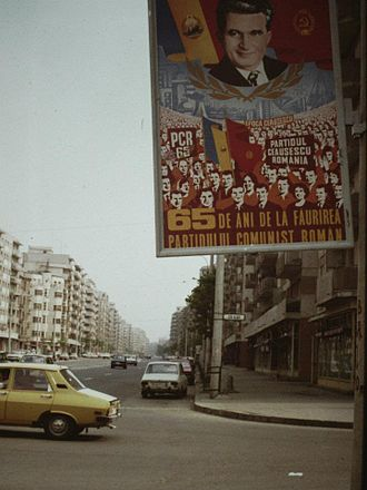"Nicolae Ceaușescu's cult of personality - A propaganda poster on the streets of Bucharest, 1986. The caption reads ""65 years since the creation of the Romanian Communist Party"", while in the background it reads ""Ceauşescu Era"" and ""The Party. Ceauşescu. Romania"""