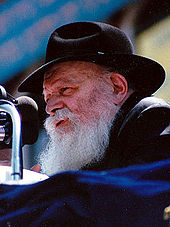 Chest high portrait of Rabbi Menachem Mendel Schneerson wearing a black hat