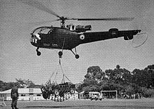A green helicopter marked with a blue-white-red roundel; the roundel of the Federal Rhodesian Air Force. Against a backdrop of observers and barracks, it is lifting a Rhodesian Army jeep via a cargo net.