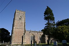 Stone building with square three stage tower at the left hand end. Trees to the right and gravestones in front.