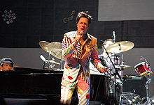 A man wearing a striped multi-colored suit with his eyes closed, singing into a microphone on a stage. Behind him is a man sitting behind a drum set and a man sitting at a piano.