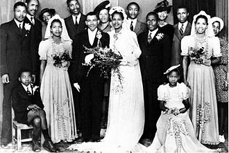 Albertina Sisulu - Walter and Albertina Sisulu wedding with Nelson Mandela and Anton Lembede. Lembede died in 1947. Evelyn Mase is to the left of the bride and Lembede is to the right of the bride. Nelson Mandela is far left. Rosabella Sisulu looks out over the couple.