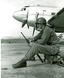 A man sits on equipment with an aircraft in the background.