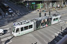 An overhead view of a white streetcar crossing an intersection, passing under traffic signals.