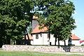 Stębark - fragment ogrodzenia i kościół Św. Trójcy (widok z boku).jpg