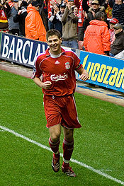 A young man with brown hair in red football kit jogging alongside the touch-line of a football pitch