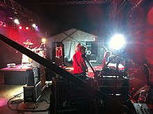 The band is seen in right profile. Robertson is at left and obscured by his drum kit and stage structures. Smith has his back to the viewer and is partly obscured by a microphone stand. Stack is further away and mostly blocked by Smith. Thistlethwayte is behind a keyboard at front of the stage with a microphone at his mouth. Other stage equipment is visible including bright over head lights.