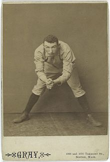 A black-and-white photograph of a man in a white baseball uniform bent over from the waist but looking into the camera