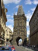Une tour de style gothique, noire, enjambe une rue. Des voitures en stationnement sont visibles au premier plan.