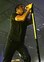 A man dressed in a black T-shirt and trousers is performing on a microphone.