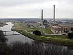 A middle-sized river flows by a factory with two tall smokestacks.