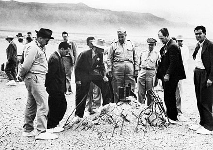 Major General Leslie Groves and Robert Oppenheimer at the Trinity shot tower remains a few weeks later. The white overshoes were to prevent the trinitite fallout from sticking to the soles of their shoes. Trinity Ground Zero.jpg