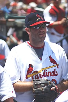 "A white man standing still and wearing a white jersey. On the jersey is a yellow baseball bat with two red birds and ""Cardinals"" in red text under it. He is also wearing a black baseball cap with a red bird on a bat, sunglasses, and a black and brown baseball glove."