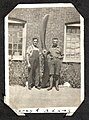 """Two men holding a large propeller in front of a brick building. The caption reads """"Corey & Adams"""" (7980780393).jpg"""