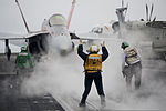 U.S. Navy Aviation Boatswain's Mate 2nd Class Tamara Sewell, center, directs an F-A-18C Hornet aircraft assigned to Strike Fighter Squadron (VFA) 94 to a catapult on the flight deck of the aircraft carrier USS 130610-N-ZI635-205.jpg