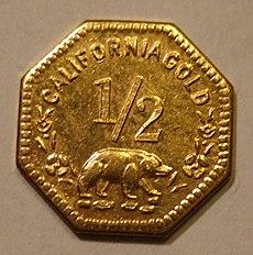 Eine achteckige Goldmünze, unter der Zahl 1/2 ist ein Bär abgebildet, darüber steht CALIFORNIA GOLD