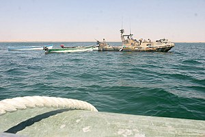 Curfew - Haditha Dam, Iraq, (September 16, 2007) – A Riverine Patrol Boat with Riverine Squadron 1, Riverine Group 1, Navy Expeditionary Combat Command, in support of Regimental Combat Team 2, tows several boats the riverines seized in support of the new 24-hour curfew enforcement of the waterway near the dam. The riverines warned locals of the new curfew for several days before seizing the boats of repeat curfew offenders