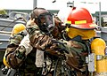 US Navy 050603-N-2385R-069 Electrician's Mate 3rd Class Michael Mosely, left, is assisted by Seaman Brent Honda assigned to Assault Craft Unit One (ACU-1) with donning his Self Contained Breathing Apparatus (SCBA).jpg