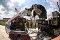 US Navy 050909-N-5526M-011 Utilitiesman 3rd Class Samuel Gutierrez from El Paso Texas assigned to Naval Mobile Construction Battalion Four Zero (NMCB-40) load metal Debris left behind from hurricane Katrina.jpg