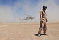 US Navy 070516-N-6597H-339 Explosive Ordnance Disposal 1st Class William Eisenhart, attached to Explosive Ordnance Disposal Mobile Unit 3 turns away from a cloud of dust during fast roping evolutions for a basic tactical traini.jpg