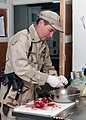 US Navy 071030-N-7415V-007 Culinary Specialist 2nd Class Timothy Wright, assigned to the Combined Security Transition Command-Afghanistan, cuts up pomegranates to put out as a snack.jpg