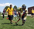 US Navy 090506-N-3038C-438 Navy Cryptologic Technician Technical First Class Ryan Candelaria cheers on a Clyde Miller Elementary School student during a Denver Navy Week firefighting relay.jpg