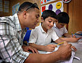 US Navy 090617-N-8053S-088 Cryptological Technician (Technical) 1st Class Daryl Maynes, assigned to U.S. Naval Forces Central Command, helps a student with his math at the Regional Institute for Active Learning in Adliya, Bahra.jpg