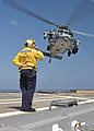 US Navy 110325-N-7293M-183 Aviation Boatswain's Mate (Handling) 2nd Class Matthew Kolb salutes an MH-60S Sea Hawk helicopter assigned to Helicopter.jpg