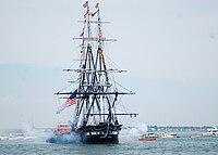 Фотография корабля без парусов.  С левой и правой стороны корабля идет белый пушечный дым.  Буксир рядом