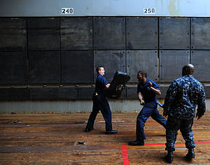US Navy 120201-N-LP801-387 Operations Specialist 3rd Class Brian Daniels demonstrates defensive maneuvers after being sprayed with oleoresin capsic.jpg