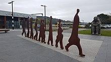 rautaoksidi-metalliveistos, joka kuvaa abstraktia hahmoa, joka kävelee yhtenä tiedostona, kivipurkaus äidin ja kahden lapsen takana, yhden kerroksen rautatieaseman rakennuksen sisäänkäynti vasemmalla