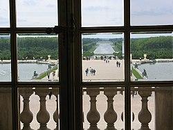 Photographie. Vue sur les parterres d'eau, le parc et le Grand Canal depuis la fenêtre centrale de la galerie. On remarque l'alignement selon d'axe est-ouest.