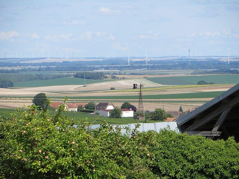 Une éolienne rouillée devant un parc d'éoliennes neuves