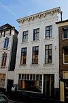 foto van Hoog huis met schilddak en met gepleisterde lijstgevel waarin fraaie empire schuiframen