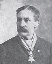 Head and shoulders of a white man with parted hair and a large mustache, wearing a star-shaped medal from a ribbon around his neck.
