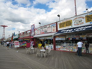 Shops along the boardwalk, with the Parachute Jump, a tall red truss structure, in the background