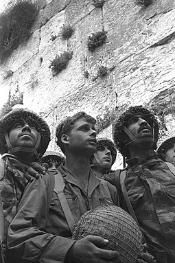 David Rubinger's photograph of IDF paratroopers at Jerusalem's Western Wall shortly after its capture. The soldiers in the foreground are (from left) Zion Karasenti, Yitzhak Yifat, and Haim Oshri. TSnKHnym bkvtl hm`rby.jpg
