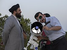 One man watches another, who looks through a modern telescope
