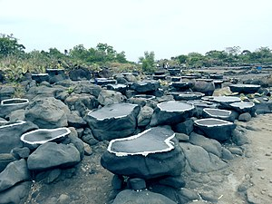 Yangpu Ancient Salt Field - Stones are cut flat on top with a thin rim. Seawater remains from high tide. It then evaporates leaving the salt, which is collected.