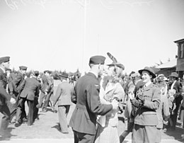 Man in dark military uniform in the arms of a female civilian, among a crowd of other civilian and military people
