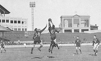 Interstate matches in Australian rules football - Players contest a mark at the Australian Football Carnival, in 1933, at the Sydney Cricket Ground. The teams are Victoria and Tasmania. (Photographer: Sam Hood.)