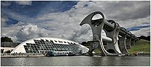 The Falkirk Wheel dominates the right of the picture with the tourist shop and restaurant dwarfed by the Wheel on the left, the bottom shows the marina with a boat in the centre