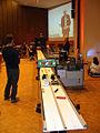 2012-11-13, e, KinderUniHannover Audimax Leibniz Universität Dr.-Ing. Mirko Schaper vor Formel 1-Rennbahn und auf dem Übertragungs-Bildschirm.jpg