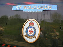 A 'Battle of Britain' class enamelled metal nameplate and crest mounted on flat metal casing covering the locomotive boiler. The nameplate forms a representation of aircraft wings, with a small rectangle attached to the middle-lower edge allowing identification as a member of the 'Battle of Briain' class. Below this is an oval-shaped plate with a crest.