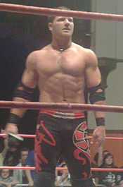 A white male wearing black and red wrestling gear standing in a wrestling ring.